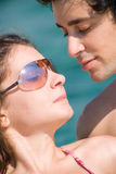 Summer couple tanning on the beach. Man looking at woman in bikini while she enjoys the sun Royalty Free Stock Images