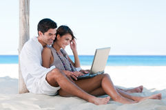Summer couple using laptop. Happy smiling couple surfing the net and enjoy the summer at tropical beach Royalty Free Stock Images
