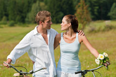 Summer - Couple walking with old bike in meadow Stock Image