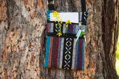 Summer creative activity and work at the park. Small colorful ethnic bag with notebook, pen, pencil and yellow flower handing on the tree. Summer creative stock image