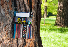 Summer creative activity and work at the park. Small colorful ethnic bag with notebook, pen, pencil and yellow flower handing on the tree. Summer creative stock photos