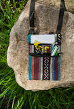 Summer creative activity and work at the park. Small colorful ethnic bag with notebook, pen, pencil and yellow flower lying on the grey stone on green grass stock image