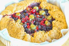 Summer crostata or galette pie with fresh garden berries. Over rusty wooden background. French cuisine - Breton galette. Sweet open pie stock image