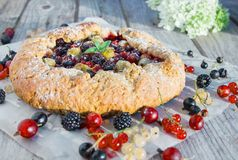 Summer crostata or galette pie with fresh garden berries. Over rusty wooden background. French cuisine - Breton galette. Sweet open pie stock images