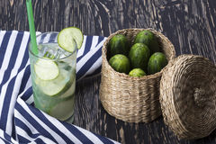 Summer cucumber cocktail and cucumbers in the basket. royalty free stock image
