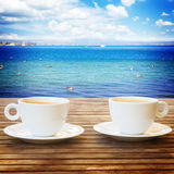 Summer cup of coffee. Two white cups of coffee on wooden table with sunny summer beach in background Royalty Free Stock Image