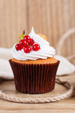 Summer cupcake with whipped cream and fruits on wooden backgroun Royalty Free Stock Image