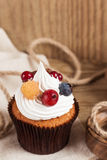 Summer cupcake with whipped cream and fruits on wooden backgroun Stock Images