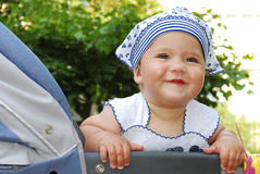 In summer,  cute little girl sitting in a pram and smiling. Royalty Free Stock Photos