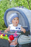 In summer,  cute little girl sitting in a pram and smiling. Stock Image