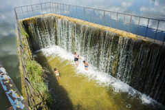 In the summer on the dam people swim under the streams of water. Royalty Free Stock Photography