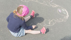 Summer day on asphalt with chalk draws a mother a baby girl. The baby girl draws mother on the pavement a Sunny day Royalty Free Stock Photo
