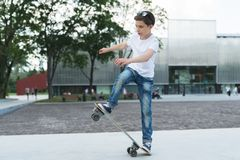 Summer day. The boy is a teenager dressed in a white T-shirt and jeans, skating, doing tricks. In the background is a modern glass building. Vacation stock photo
