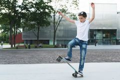 Summer day. The boy is a teenager dressed in a white T-shirt and jeans, skating, doing tricks. In the background is a modern glass building. Vacation Royalty Free Stock Images