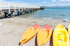 Summer day at Days Bay and wharf Wellington, New Zealand beach,. With kayaks, beach equipment and long wharf Royalty Free Stock Photo