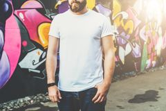Front view. Young bearded hipster man dressed in white t-shirt is stands against wall with graffiti. Mock up. Royalty Free Stock Images