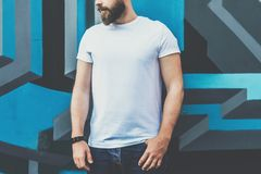 Front view. Young bearded hipster man dressed in white t-shirt is stands against wall with graffiti. Mock up. Summer day. Front view. Young bearded hipster man Stock Image