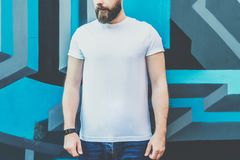 Front view. Young bearded hipster man dressed in white t-shirt is stands outdoor against wall with graffiti. Mock up. Royalty Free Stock Photos