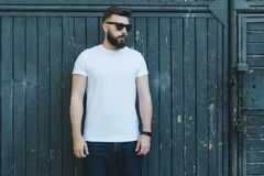 Front view. Young bearded hipster man dressed in white t-shirt and sunglasses is stands against dark wood wall. Summer day. Front view. Young bearded hipster royalty free stock images