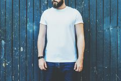 Front view. Young bearded hipster man dressed in white t-shirt and sunglasses is stands against dark wood wall. Stock Image