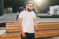 Front view. Young bearded hipster man dressed in white t-shirt and sunglasses is stands on city street. Mock up. Stock Image
