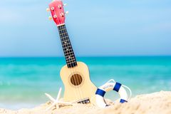The Summer day with Guitar ukulele for relax on the beautiful beach and blue sky background,. Copy space. Travel and Summer Concept Royalty Free Stock Image