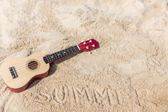 The Summer day with Guitar ukulele for relax. On the beautiful beach and blue sky background,copy space. Travel and Summer Concept Stock Image