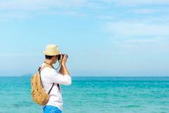 Summer Day.  Happy smiling caucasian tourist asian young man holding camera Royalty Free Stock Images