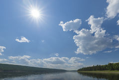 Summer day landscape with river, forest, clouds on the blue sky and sun. Stock Photos