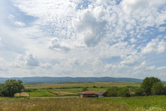 Summer day landscape with road, cloudy sky and small houses. Ukraine, Carpathian. Royalty Free Stock Image
