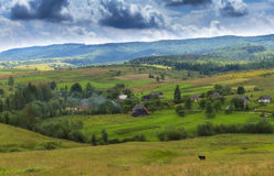 Summer day landscape with road, cloudy sky and small houses. Ukraine, Carpathian. Royalty Free Stock Photography