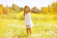 Summer day little girl having fun. Soap bubbles Royalty Free Stock Photography