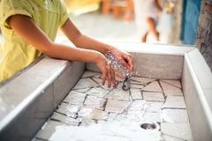 Summer day. Little girl playing with water. Close up. Copy space Royalty Free Stock Images