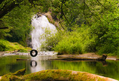 Summer Day Off. A perfect day off, swing from an old tire swing above a quiet creek and a great view of a water fall Royalty Free Stock Images