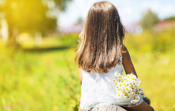 Summer day, silhouette little girl. With flowers enjoying nature Stock Image