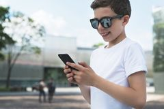 Summer day. Smiling boy in white T-shirt and sunglasses stands outdoor and uses smartphone. Boy plays computer games Royalty Free Stock Images