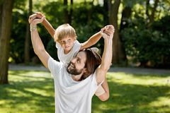 Summer day. Smiling handsome man with dark hairs and beard is holding little boy on his back. stock images