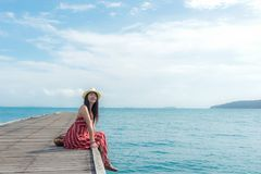 Summer Day. Smiling women relax and wearing red dress fashion sitting on the wooden bridge over the sea, blue sky background. Stock Photography