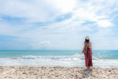Summer Day.  Smiling woman wearing fashion summer standing and see the sandy ocean beach. Happy woman enjoy and relax vacation. Stock Image