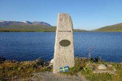 Stone marking the border crossing between Sweden and Norway at E12 road to Mo I Rana. Umbukta lake in the back royalty free stock photos