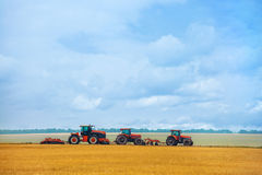 Summer day three tractor with plow standing on the sloping wheat field before the beginning of the work. Stock Photo