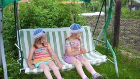 Two girls sisters swing on a swing. Entertainment and outdoor recreation. Summer day. Summer day. Two girls sisters swing on a swing. Entertainment and outdoor stock video