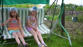 Two girls sisters swing on a swing. Entertainment and outdoor recreation. Summer day. Summer day. Two girls sisters swing on a swing. Entertainment and outdoor stock video footage