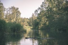 Summer day on water in calm river enclosed in forests with sandstone cliffs and dry wood - vintage retro film look. Summer day on water in calm river enclosed in royalty free stock images