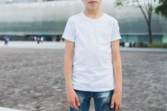 Young hipster boy dressed in white t-shirt is stands outdoor. Mock up. Space for logo, text, image. Stock Image