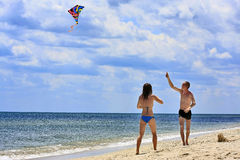 Summer days. Young couple flying a kite on the beach Royalty Free Stock Photo