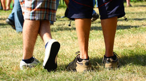 Summer days relaxing. Boys legs in shorts on a field royalty free stock photo
