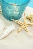 Summer decoration with copy space. Starfish and seashells on sand with candle Copy space Royalty Free Stock Images