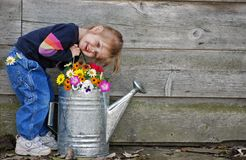 Little girl with watering can. Little girl with summer flowers in a watering can stock photography