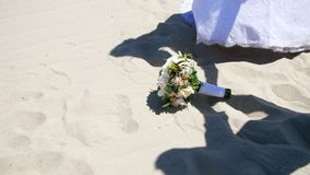 Summer, desert, against the background of sand, and the wedding bouquet lying on it, shadows, outlines of people in stock video footage